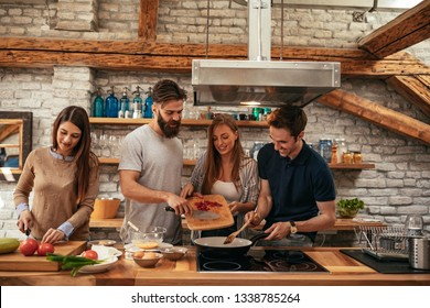 Cheerful group of friends making a delicious meal at home