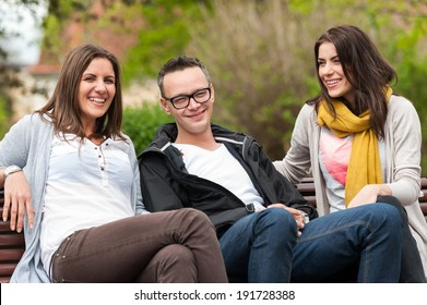 Cheerful group of friends, one man and two women sitting outdoor on a bench in park ,talking having fun, laughing smiling happy.