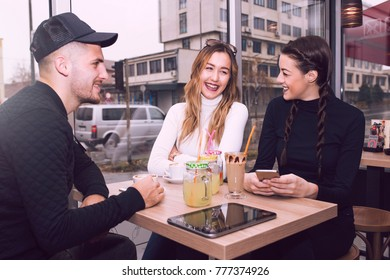 Cheerful group of friends, one man and two women sitting at the table in the cafe shop,  talking and having fun laughing smiling happy.