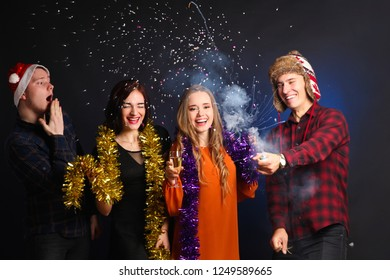 Cheerful group of friends with petard and confetti on black background. Concept New Year.