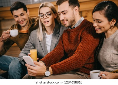 cheerful group of friends taking selfie and holding drinks