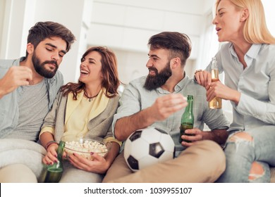 Cheerful group of friends watching football game on tv,having fun at home.