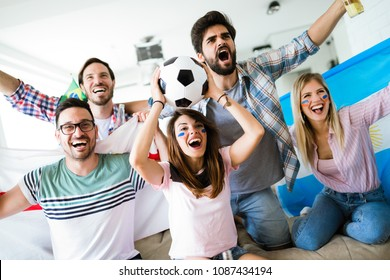 Cheerful group of friends watching football game on tv.