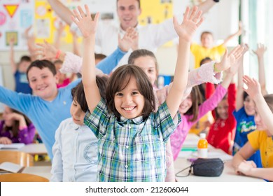 Cheerful group of kids wtih their teacher in school classroom