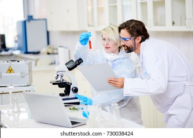 Cheerful group of microbiologists wearing safety goggles looking at test tube proudly while working together on creation of brand new cancer vaccine, interior of modern laboratory on background