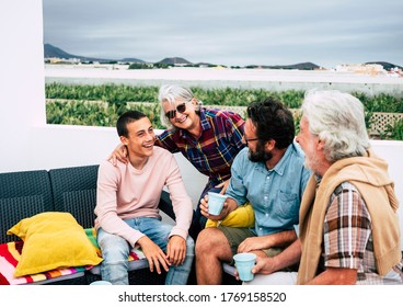 Cheerful group of multi-generation family having fun together outdoor on terrace. Four people from senior grandparents to son and grandson