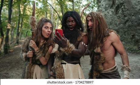 Cheerful group of neanderthal hunters using modern technology smartphone cheering up walking outside cave in the jungle. Technology and first people.