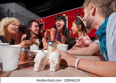 Cheerful group of people with pizza slices outside near food truck
