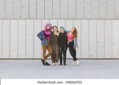 cheerful group of teen women hugging and showing their friendship isolated on a grey wall