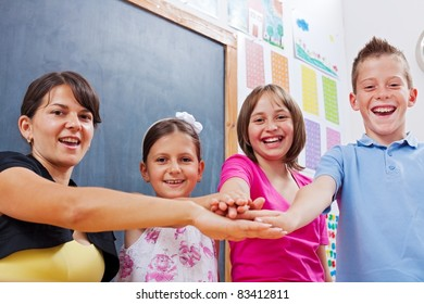 Cheerful group of united students and teacher, putting their hands together