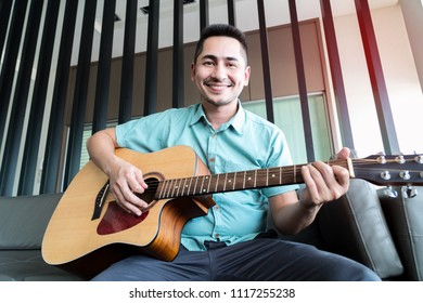 Cheerful guitarist. Cheerful handsome young man playing guitar and smiling while sitting at room