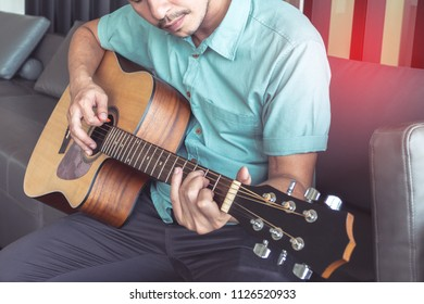Cheerful guitarist. Cheerful handsome young man playing guitar sitting at room