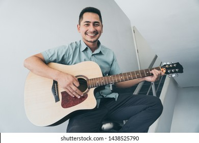 Cheerful guitarist. Cheerful handsome young man playing guitar and smiling while sitting on banister, process color and effect grain.