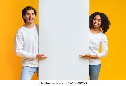 Cheerful Guy And Afro Girl Holding And Pointing At White Advertisement Board, Standing Together Over Yellow Background