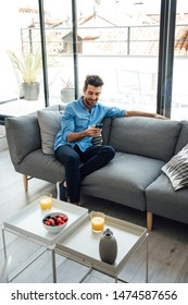 Cheerful guy in casual outfit smiling and browsing smartphone while resting on sofa in living room of penthouse apartment