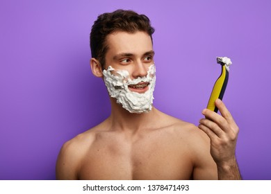 cheerful guy expresses positive emotion, rejoices at good modern shaver, looking at it, happy for the result of shaving.close up phot. isolated on the blue background