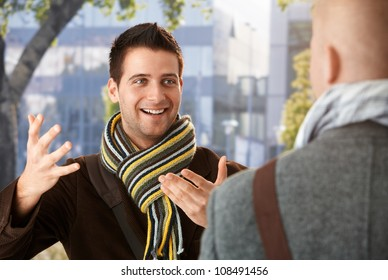 Cheerful guy gesturing to friend in conversation, standing outdoors, wearing scarf, smiling.