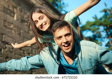 Cheerful guy with a girl on a wall background