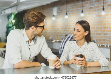 Cheerful guy and girl resting in cafeteria