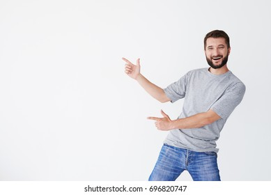 Cheerful guy pointing with both hands on white background aside, bending back a bit, mid shot