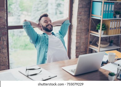 Cheerful guy is resting in front of his laptop screen, at his work place, with arms behind the head, smiling, with closed eyes, serene and peaceful break in the home office
