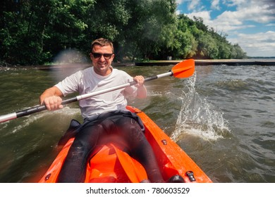 cheerful guy sits in a red kayak and row with a paddle