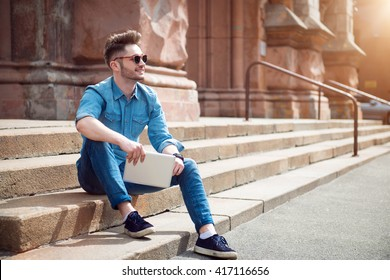 Cheerful guy sitting on the footsteps