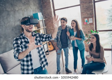 Cheerful guy wearing virtual reality goggles, getting experience using VR-headset, gesticulating, touching something with arms in office during coffee break