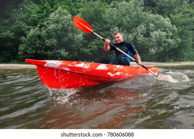 cheerful guy in a wetsuit sits in a red kayak and row with a paddle