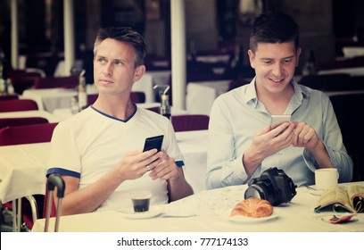 Cheerful guys looking at smartphones and drinking coffee with bakery