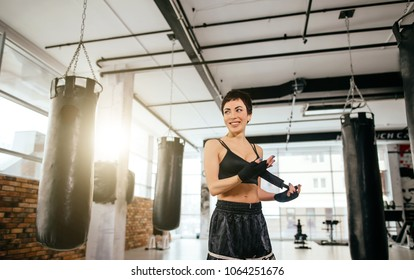 cheerful gymnast with ideal body preparing for gymnasium exercises at fitness club with panoramic window.regular training.being interested in sport