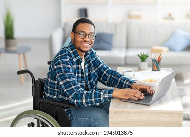 Cheerful handicapped black man in wheelchair using laptop for online job from home, having business meeting on web. African American disabled freelancer working on remote project