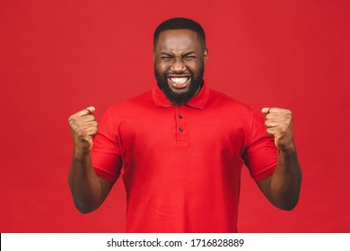 Cheerful handsome African american man making yes gesture while excited about winning. Ecstatic young fan rooting and expressing support. Success concept.