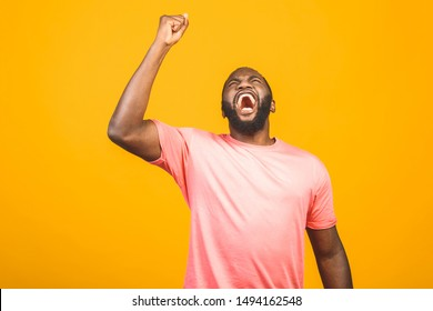 Cheerful handsome African guy making yes gesture while excited about winning. Ecstatic young fan rooting and expressing support. Success concept.