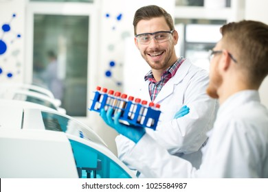 Cheerful handsome bearded male scientist smiling talking to his colleague while working with blood test samples together at the laboratory communication teamwork experience medicine friendship intern