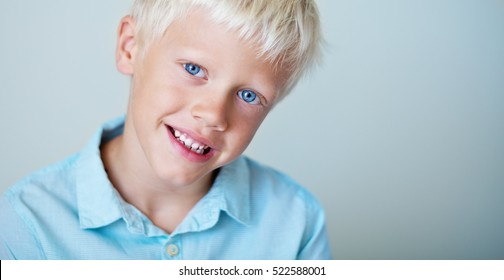 Cheerful handsome boy (7 years ) on a blue background. White hair and blue eyes. Positive child.