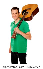 Cheerful handsome casual man with guitar on shoulders looking at camera