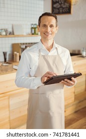 Cheerful handsome cook holding a tablet