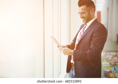 Cheerful handsome executive manager watching funny videos on touchpad having work  break standing near advertising area, positive CEO chatting with employees using wireless connection in office