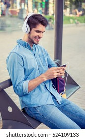 Cheerful handsome guy listening music while waiting for the bus