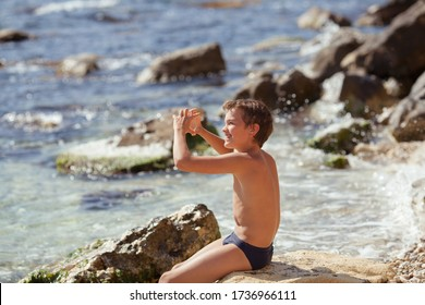 Cheerful handsome guy sitting on the stones on the seashore