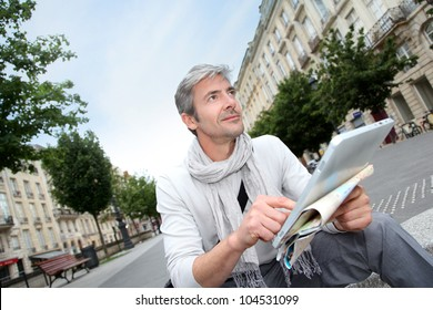 Cheerful handsome guy in town using electronic tablet