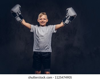 Cheerful handsome little boy boxer with blonde hair dressed in a white t-shirt wearing boxing gloves rejoices in a victory. Isolated on dark textured background.