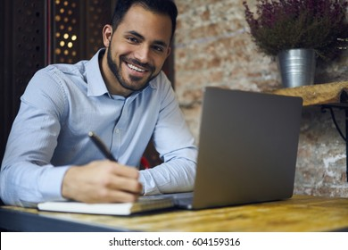 Cheerful handsome male executive manager of business enterprise having good mood doing remote job project solved problems with development sitting in coworking space using laptop computer and wifi