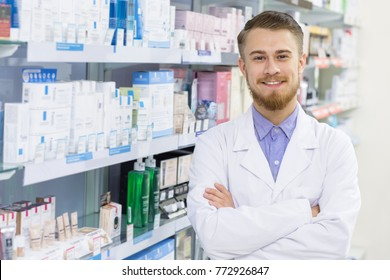 Cheerful handsome male pharmacist smiling to the camera confidently with his arms folded posing at the drugstore copyspace professional experienced medical health trustworhy friendly helpful