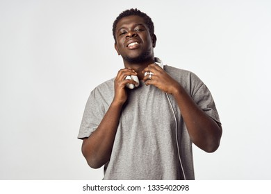 Cheerful handsome man of African appearance with headphones on a gray background - Shutterstock ID 1335402098