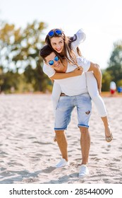 Cheerful handsome man carrying his girlfriend on his back on the beach