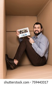 Cheerful handsome man pointing at tablet with depositphotos website sitting in cardboard box