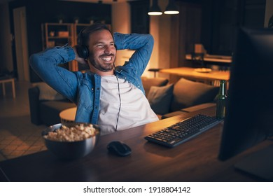 Cheerful handsome man sitting at his home office, watching funny show on computer and laughing