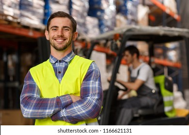 Cheerful and handsome manager of warehouse smiling, posing and looking at camera. Specialist wearing in acid green reflective waistcoat. Loader operating forklift on background.